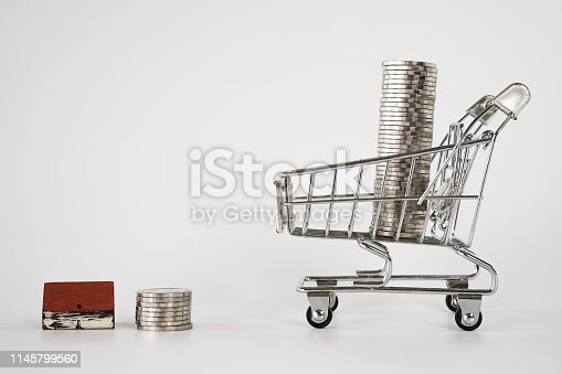 istock Wood house model on white background   and row of coin money in shopping cart  . Real Estate market, Trading Estate, Mortgage Concepts. 1145799560