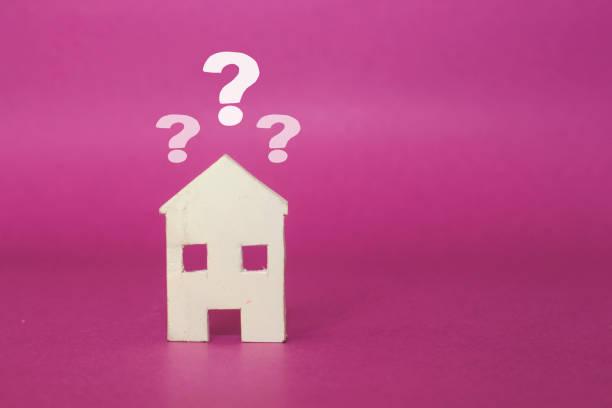 Holzhaus Modell mit Fragezeichen über rosa Hintergrund und freien Kopierraum für Ihren Text – Foto