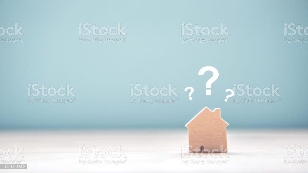 Holz hausmodell mit Fragezeichen über der hölzernen Schreibtisch und kostenloses Exemplar Platz für Ihren Text. – Foto