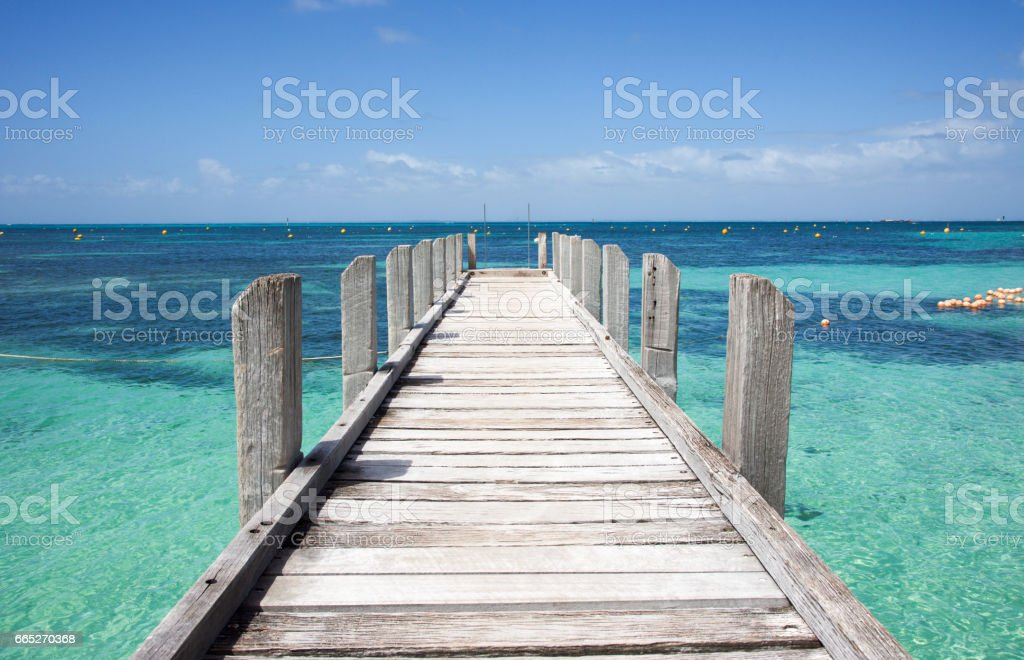 Wood jetty in diminishing perspective into the turquoise-green Indian Ocean waters off the coast of Rottnest Island in Western Australia. stock photo