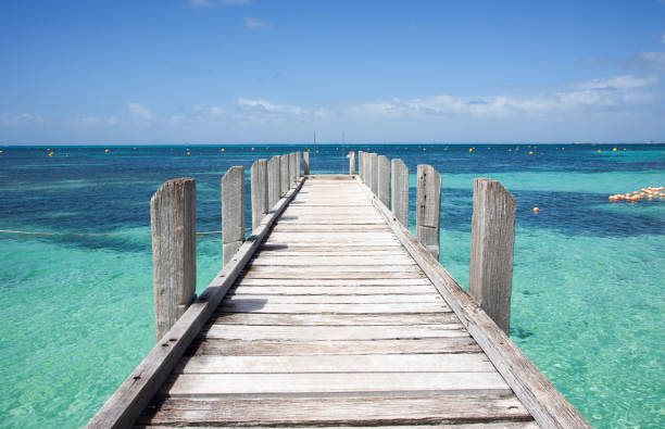 Wood jetty in diminishing perspective into the turquoise-green Indian Ocean waters off the coast of Rottnest Island in Western Australia. - foto stock