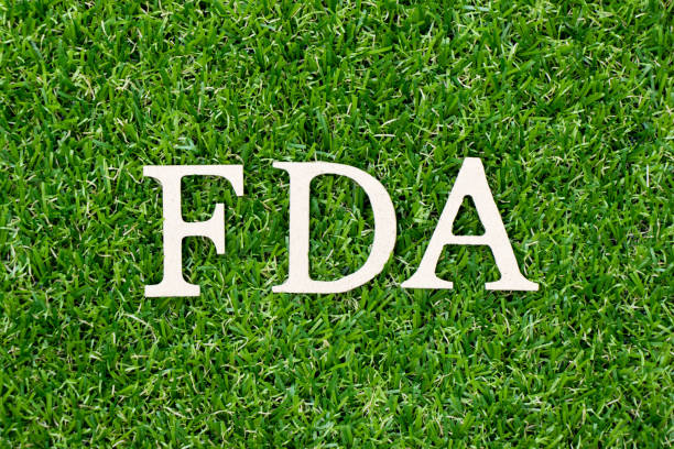 wood letter block in word fda (abbreviation of food and drug administration) on artificial green grass background - fda stock photos and pictures