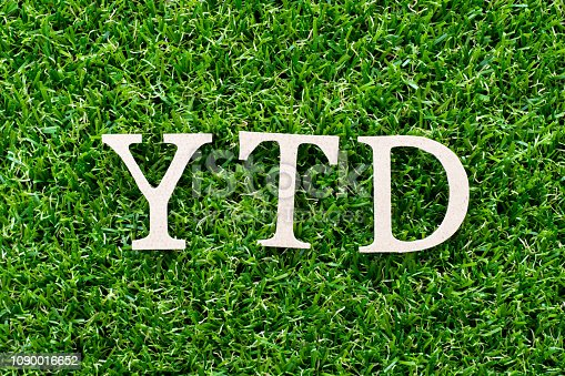 istock Wood letter in word YTD (abbreviation of year to date) on artificial green grass background 1090016652