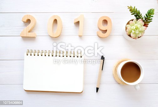 1057357020istockphoto 2019 wood letters, blank notebook paper and coffee on white table background, 2019 new year mock up, template with copy space for text, top view 1073406864