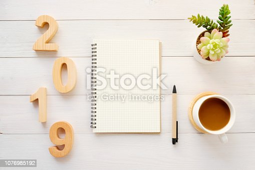 1057357020istockphoto 2019 wood letters, blank notebook paper and coffee on white table background, 2019 new year mock up, template with copy space for text, top view 1076985192