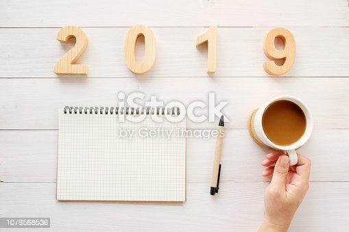 1057357020istockphoto 2019 wood letters, blank notebook paper and hand holding coffee cup on white table background, 2019 new year mock up, template with copy space for text, top view 1079568536