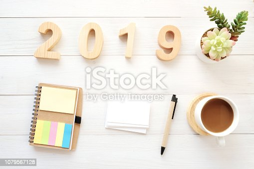 1057357020istockphoto 2019 wood letters, blank notebook paper, business card and coffee on white table background, 2019 new year mock up, template with copy space for text, top view 1079567128
