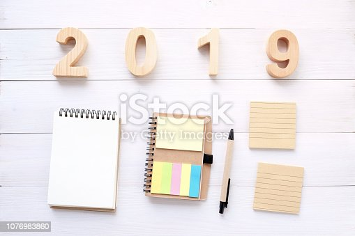 1057357020istockphoto 2019 wood letters, blank notebook paper on white table background, 2019 new year mock up, template with copy space for text, top view 1076983860
