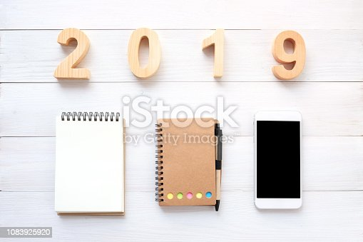 1057357020istockphoto 2019 wood letters, blank notebook paper, white smart phone with blank screen and pencil on white wood background, 2019 new year mock up, template with copy space for text, top view 1083925920