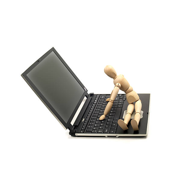 wood mannequin and laptop stock photo