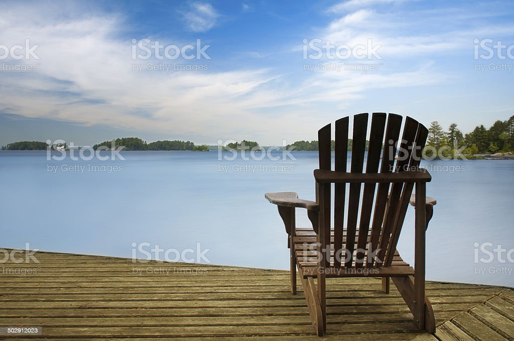 Wood Muskoka chair on a lake deck stock photo