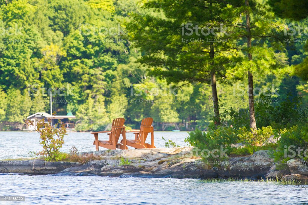 Wood Muskoka chairs facing a lake stock photo