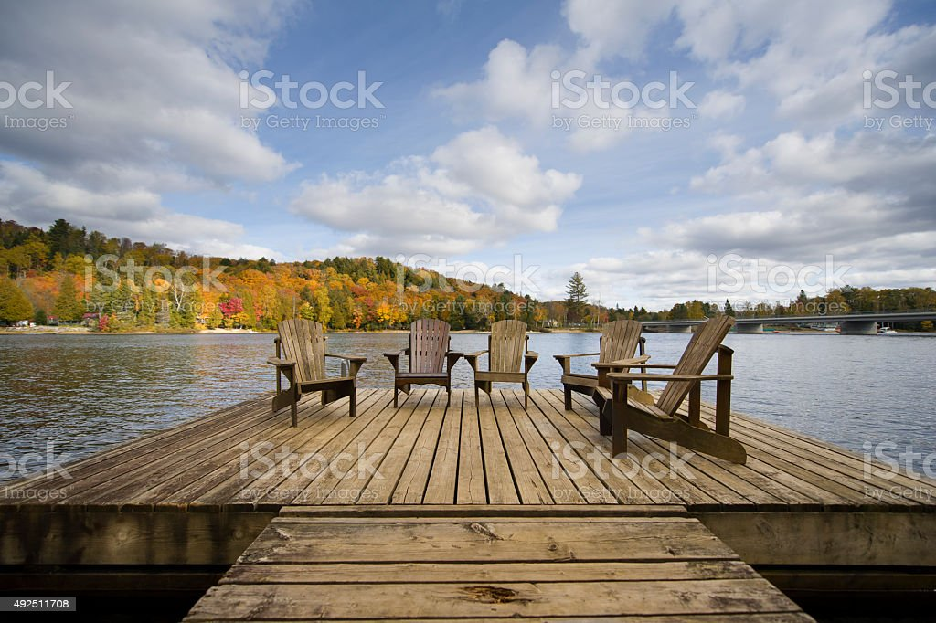 Wood Muskoka chairs on a lake deck in the Fall stock photo