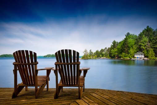 istock Wood Muskoka chairs on a lake deck 482345735