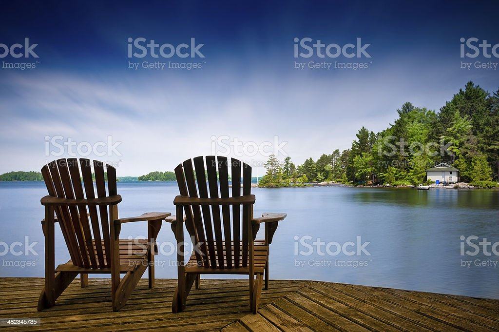 Wood Muskoka chairs on a lake deck stock photo