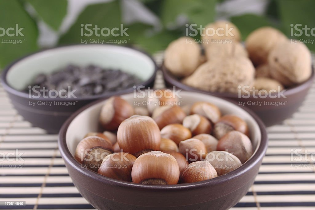 Wood nuts in cup on bamboo napkin royalty-free stock photo