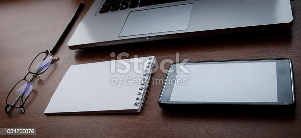 862672018 istock photo Wood office desk table with laptop, glasses, notebook, pen, smartphone. Top view, copy space. 1034700076