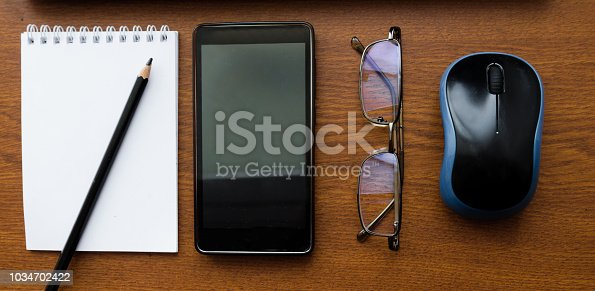 862672018 istock photo Wood office desk table with laptop, glasses, notebook, pen, smartphone. Top view, copy space. 1034702422
