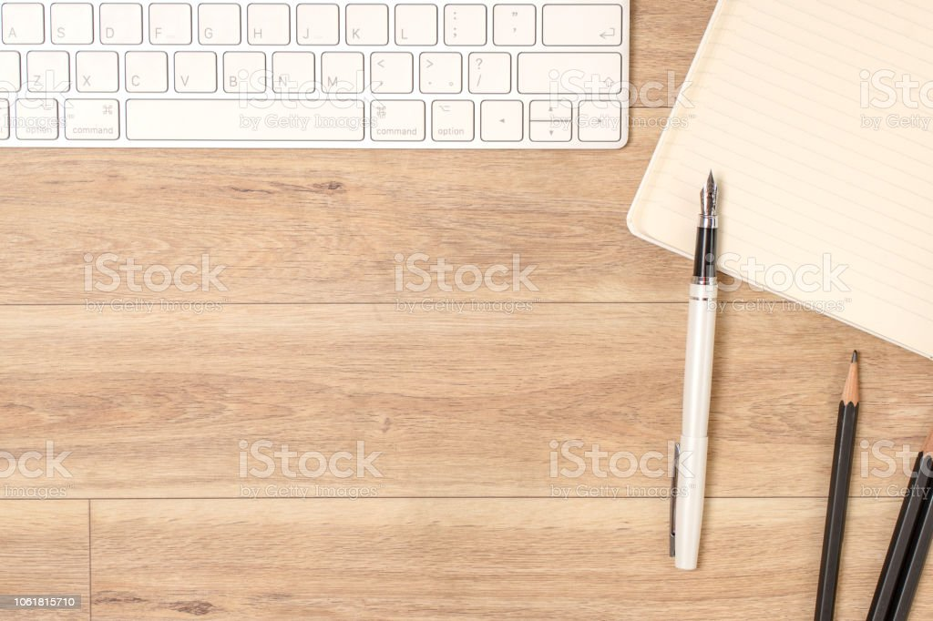 Wood office desk table with laptop, glasses, notebook, pen. Top view,...