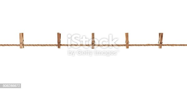 wood, old clothes pegs hanging on a rope. On white background