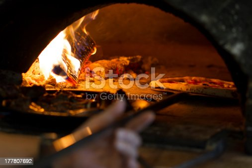 Pizza baking in wood oven.
