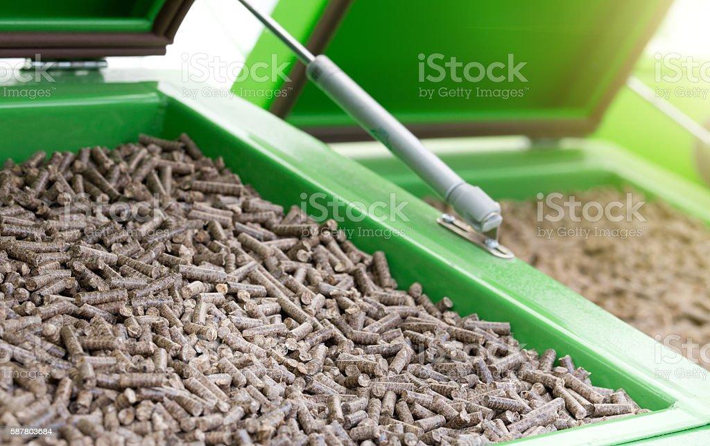 Wood pellets in green container - foto de stock