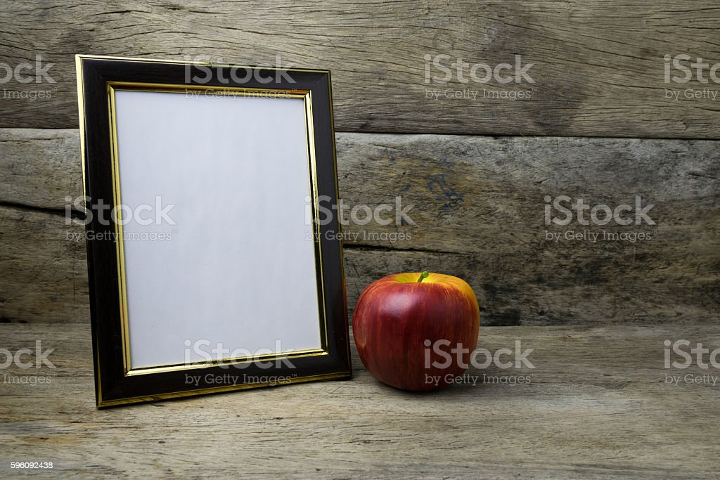 Wood photo frame and red apple on wooden table royalty-free stock photo