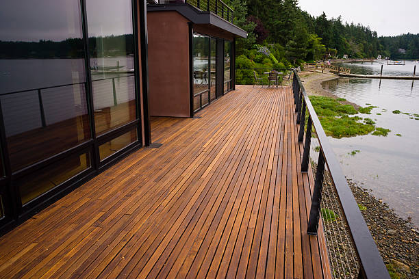 Wood Plank Deck Patio Beach Water Contemporary Waterfront Home A beautiful waterfront home has the water view from the back wood deck man made structure stock pictures, royalty-free photos & images