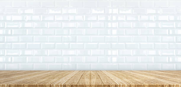 Wood plank table top at white glossy ceramic tile wall background,Mock up for display or montage of product,Banner or header for advertise on social media Wood plank table top at white glossy ceramic tile wall background,Mock up for display or montage of product,Banner or header for advertise on social media. empty desk stock pictures, royalty-free photos & images