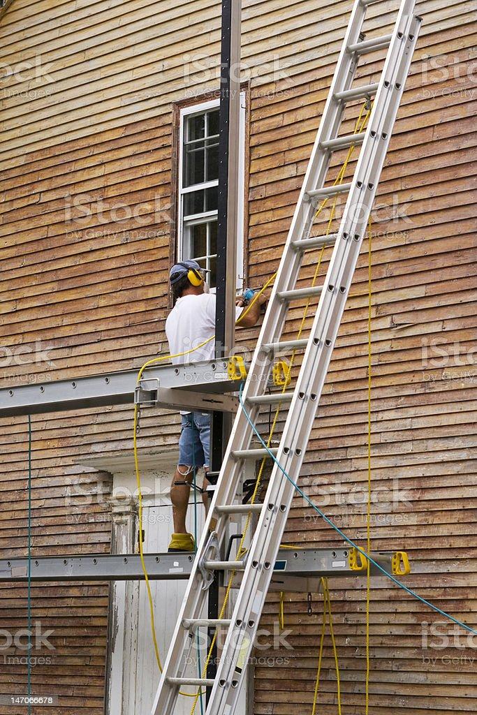 Wood sanding the house stock photo