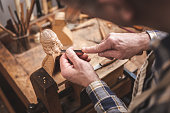 Over shoulder view of a mature man working with a carving tool on a wooden figure. He is wearing a checkered shirt standing inside a workshop. The background shows a rustic workbench.