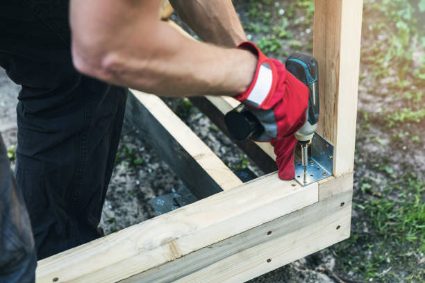 wood shed construction - man screwing corner joint brace wood shed construction - man screwing corner joint brace shed stock pictures, royalty-free photos & images