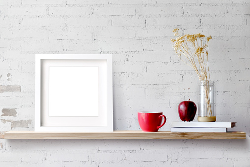 Wood shelf with blank white frame and coffee.