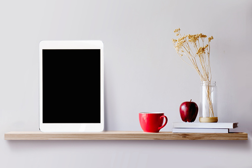 Wood shelf with tablet and coffee.