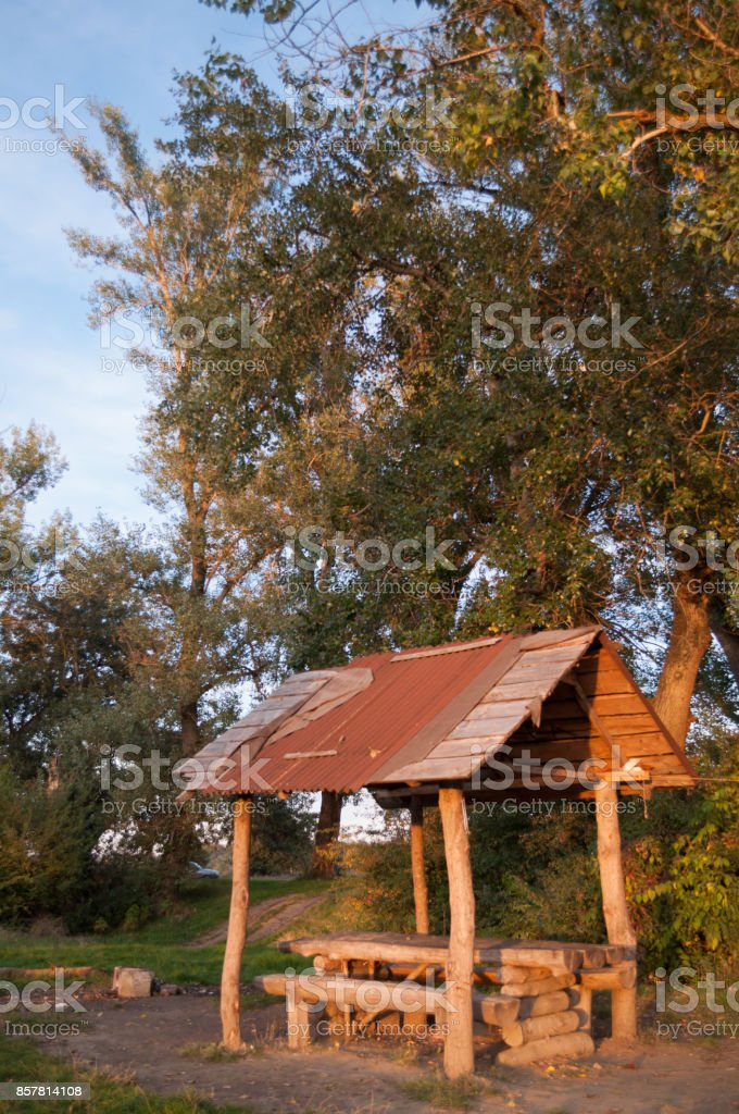 wood shelter in the forest at sunset stock photo