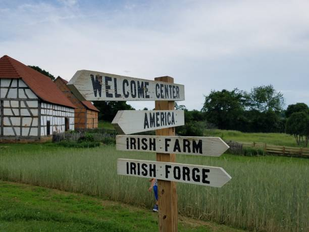 wood sign saying America, welcome center, and Irish farm, with building and grass field stock photo
