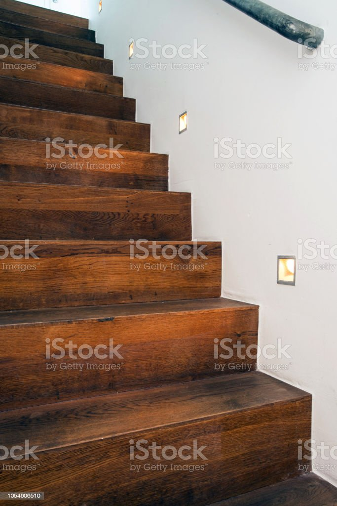Wood stairs by night with led light in the white wall modern design...