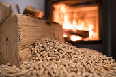 istock Wood stove heating with in foreground wood pellets 1097493356