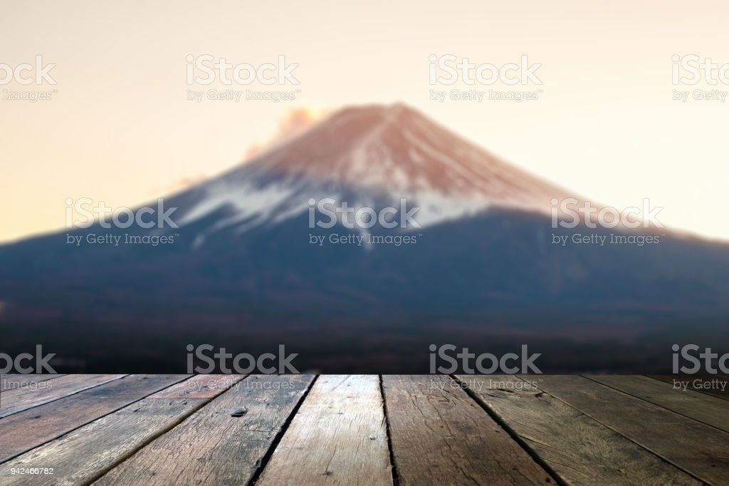 wood table and blur image of 'fuji' mountain in japan for background usage . stock photo
