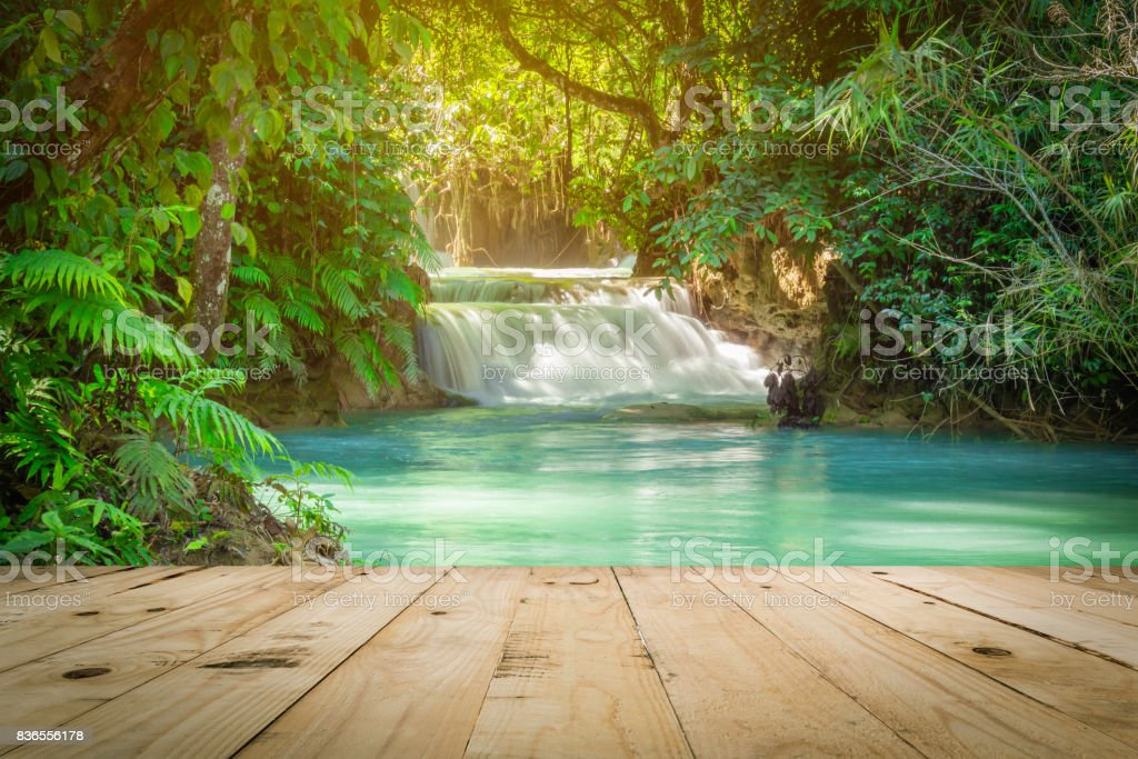 Wood table and Kuang Si waterfalls in Luang Prabang, Laos. stock photo