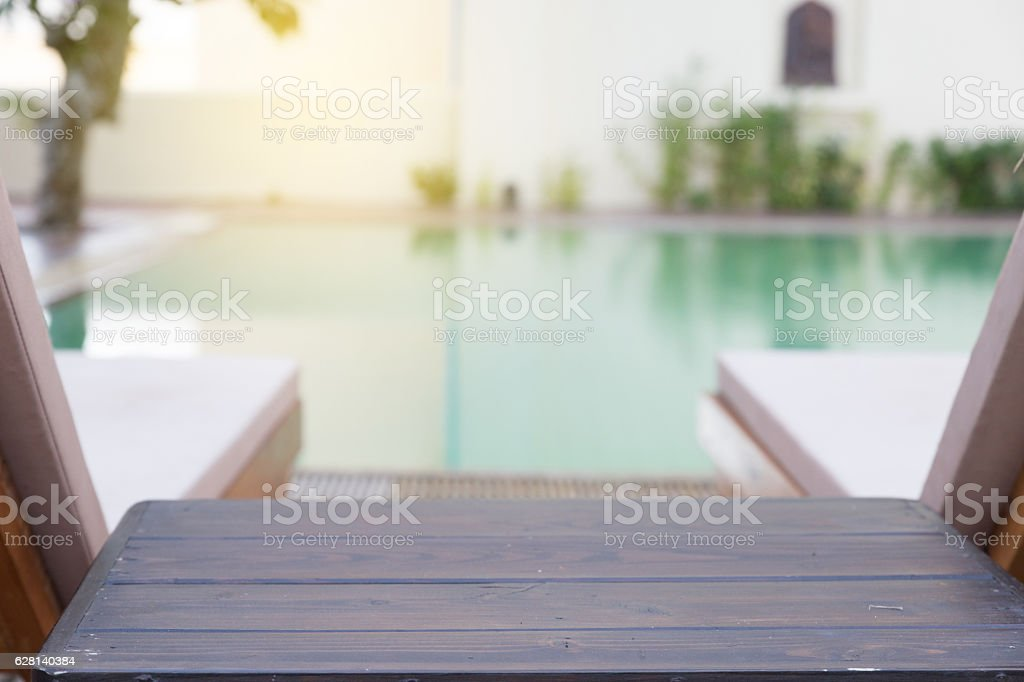 wood table and pool chair for resting and relaxing at swimming pool stock photo