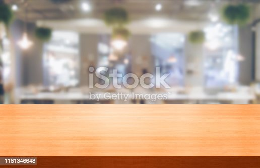 924418708 istock photo Wood table in blurry background of modern restaurant. 1181346648
