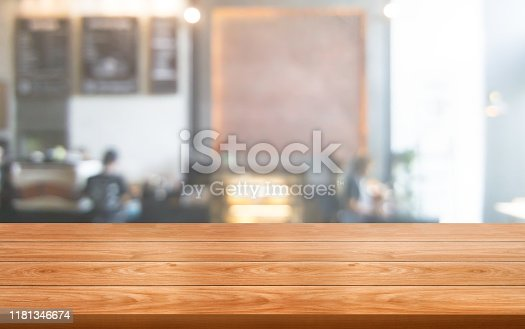 886308526 istock photo Wood table in blurry background of modern restaurant. 1181346674