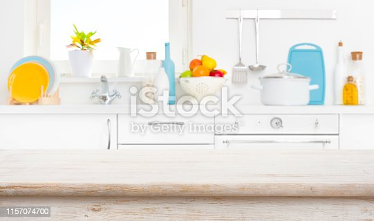 923629650istockphoto Wood table in front of blurred rustic kitchen window background 1157074700