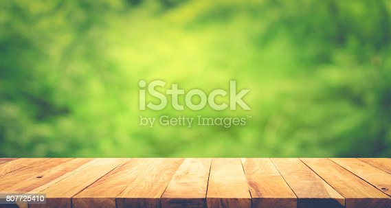 680878382istockphoto Wood table on blur green background. 807725410
