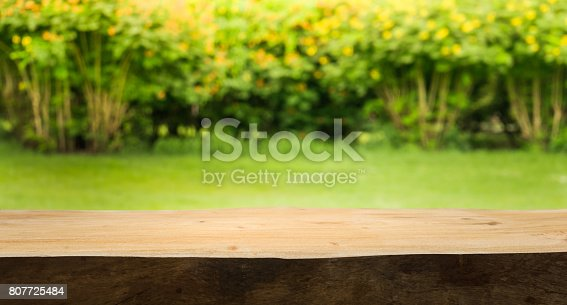 680878382istockphoto Wood table on blur green,flower from garden,park background. 807725484