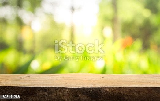 680878382istockphoto Wood table on blur green,flower from garden,park background. 808144288