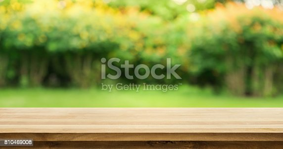 680878382istockphoto Wood table on blur green,flower from garden,park background. 810469008