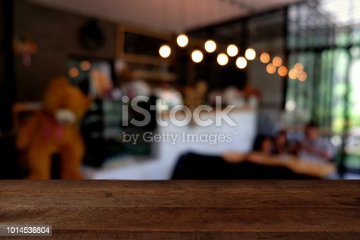 istock wood table on blur of cafe, coffee shop, bar, resturant, background - can used for display or montage your products 1014536804