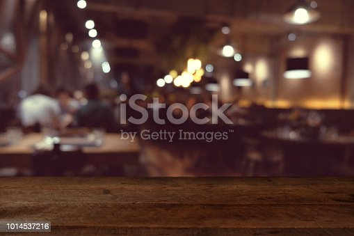 istock wood table on blur of cafe, coffee shop, bar, resturant, background - can used for display or montage your products 1014537216